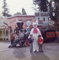 Easter Bunny poses with two children in front of Frontier Village Railroad.
